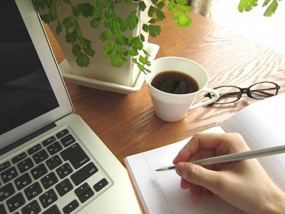 テーブルに置いてあるパソコンとコーヒー