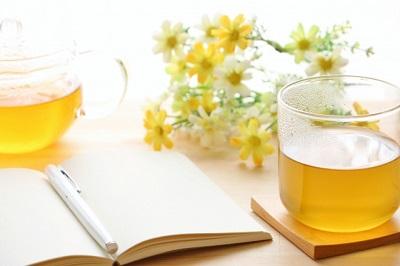 テーブルの上にある本と花とお茶